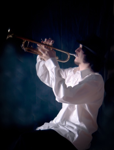 graduating high school boy posing for senior pictures with trumpet