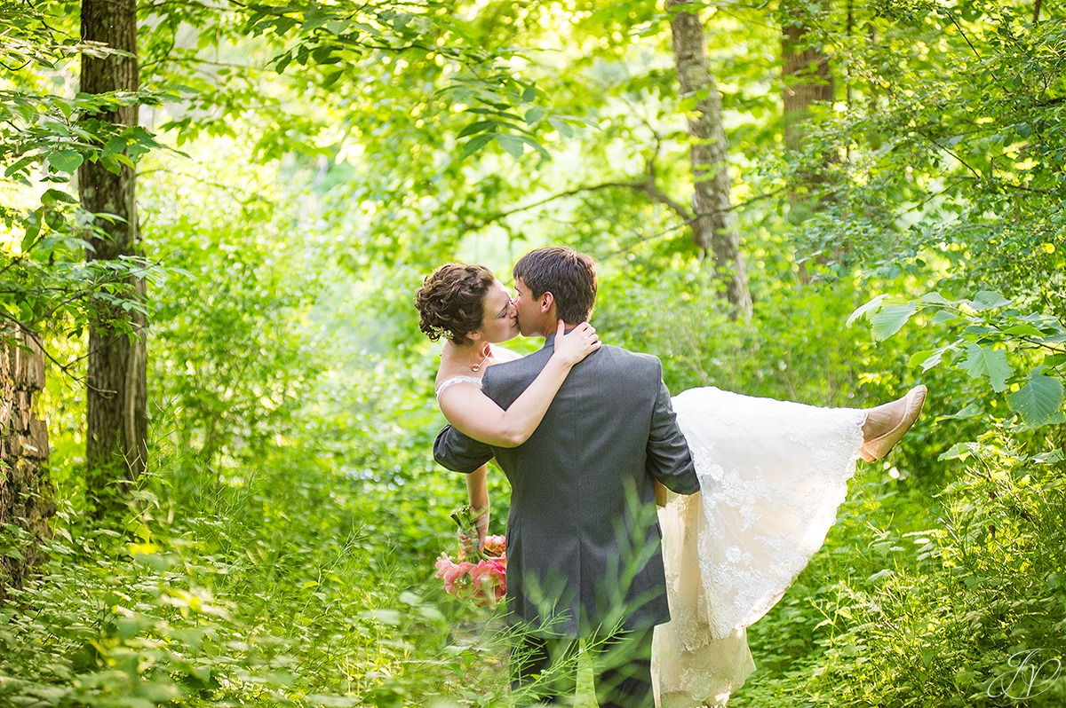 groom carrying bride through the woods