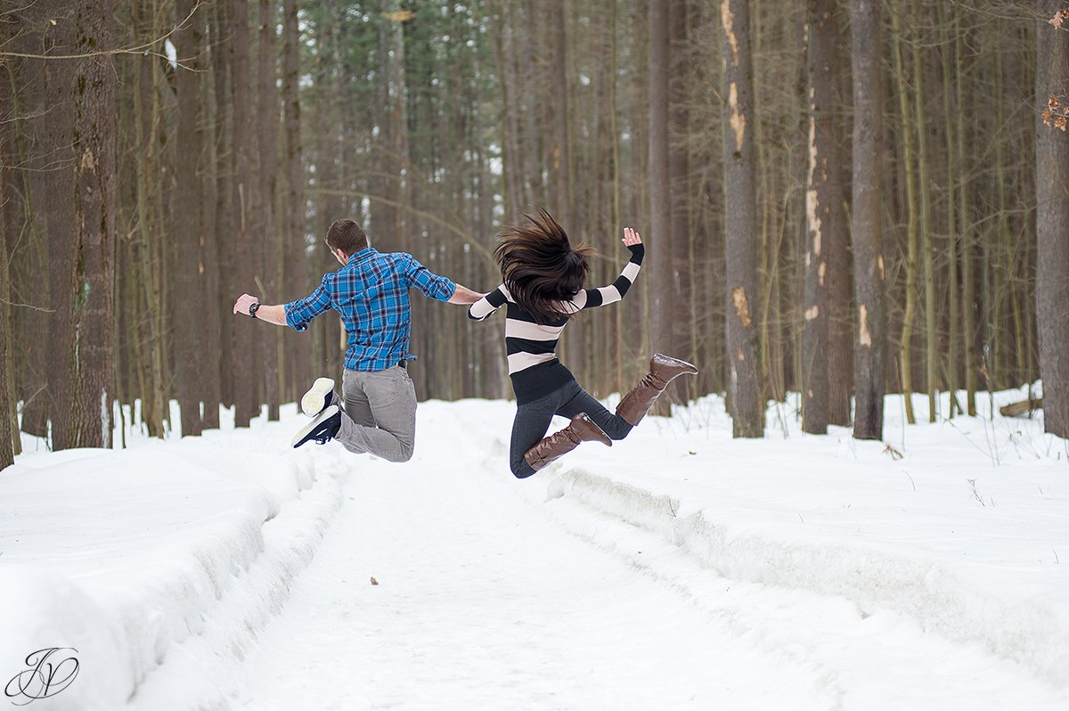 fun photo of engaged couple jumping in snow