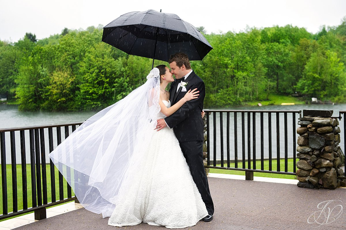 bride and groom in the rain photo, bride and groom with umbrella photos, portraits of beautiful bride and groom kissing, kissing bride and groom photo