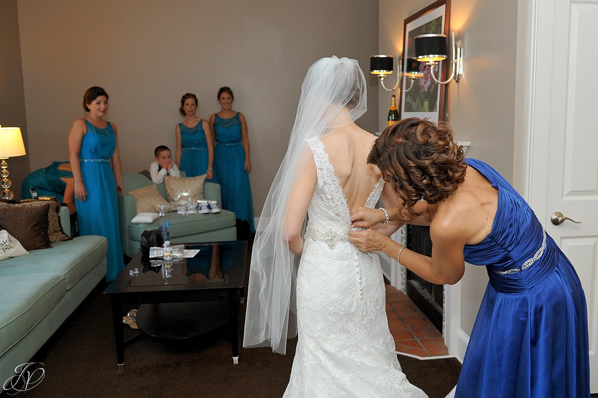 bride getting dress help from mother