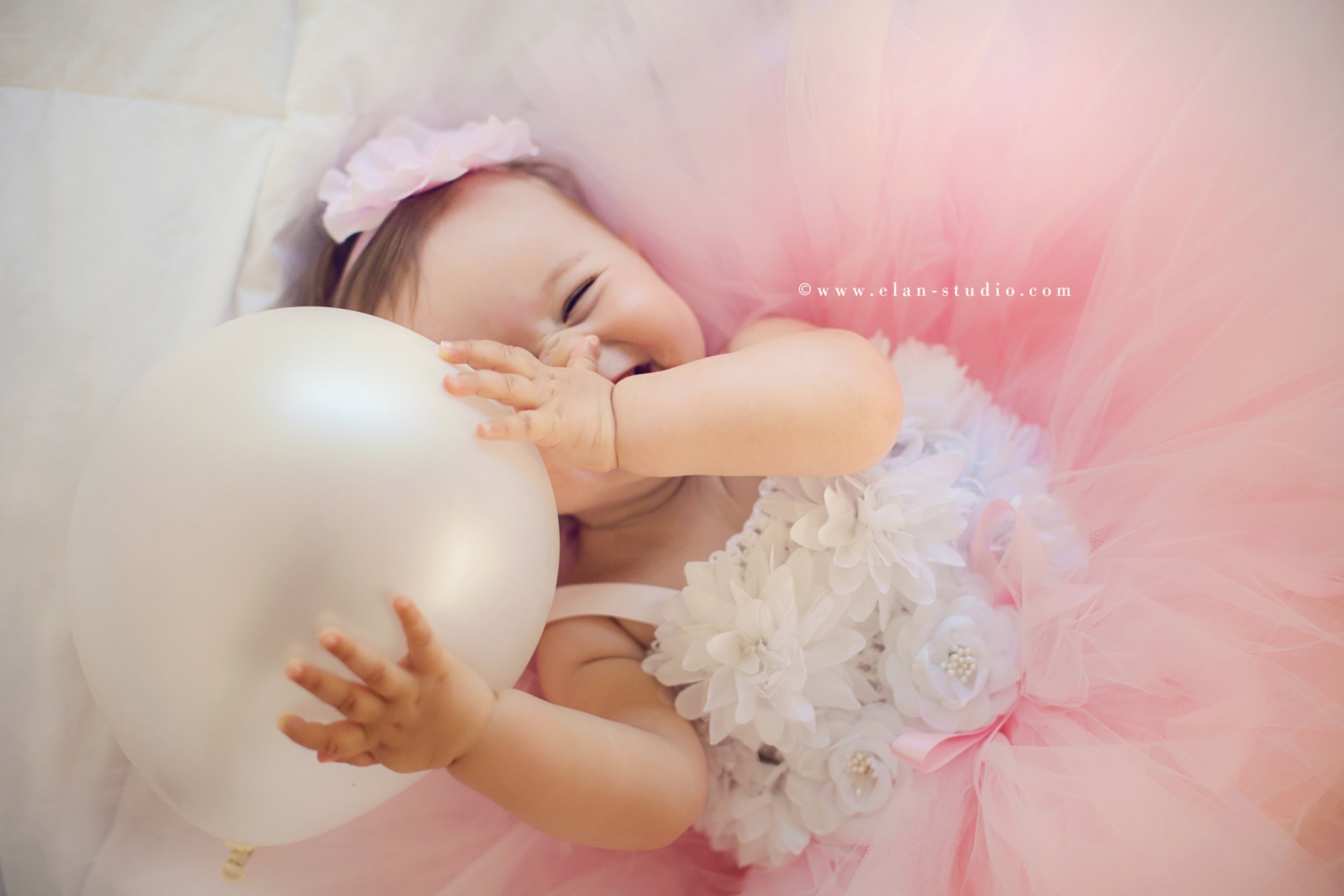 laughing baby girl with pink balloon