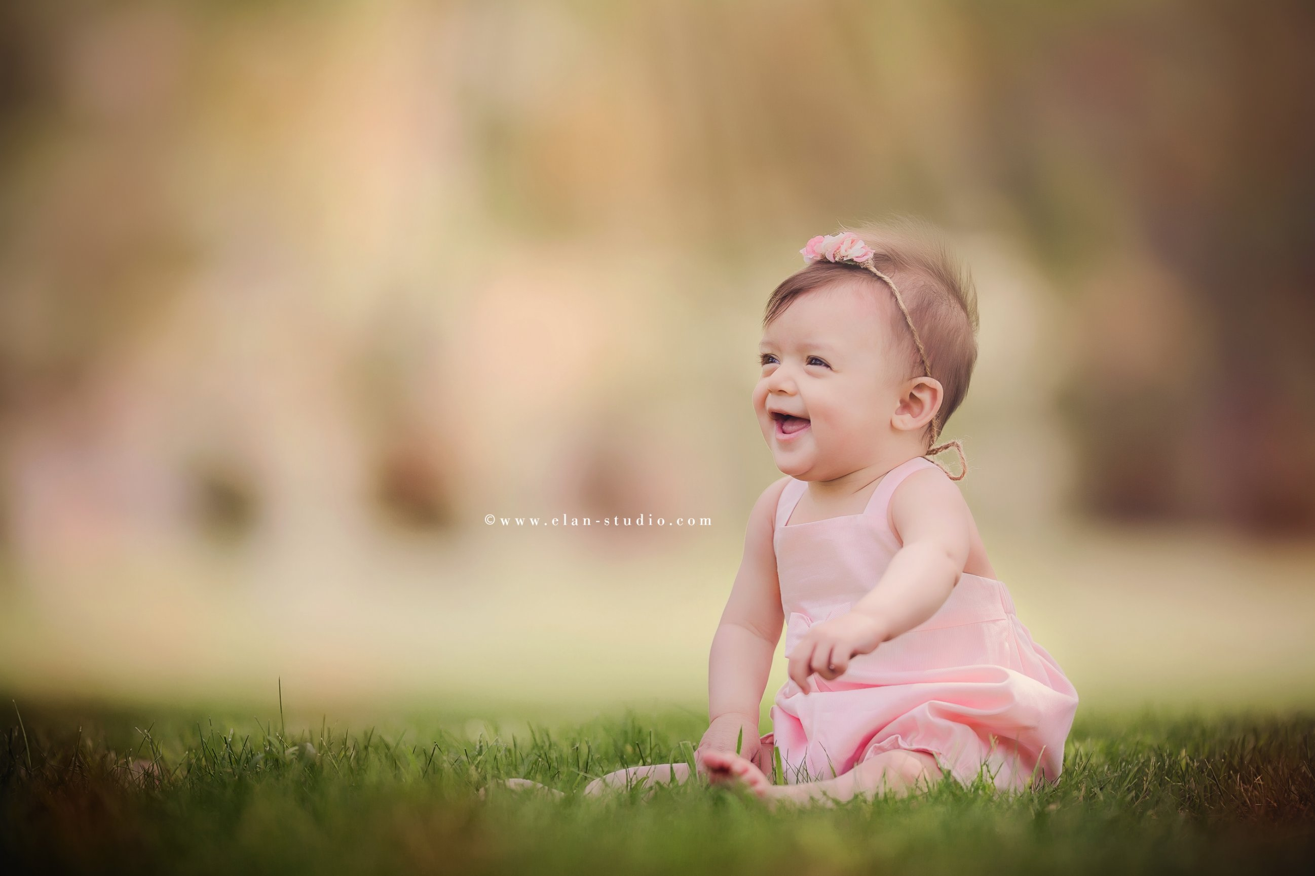 smiling sitting baby girl with a pink romper, green grass, background bokeh, Tracy Sweeney