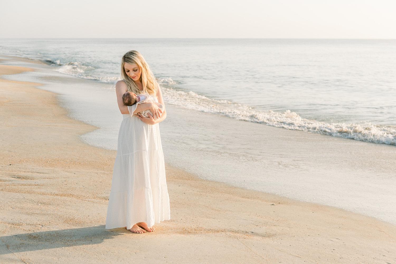 beautiful blonde mom walking on beach with newborn son, Ryaphotos