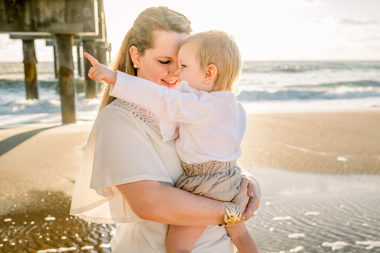 mother smiling down at baby daughter, little girl pointing at the beach, Rya Duncklee