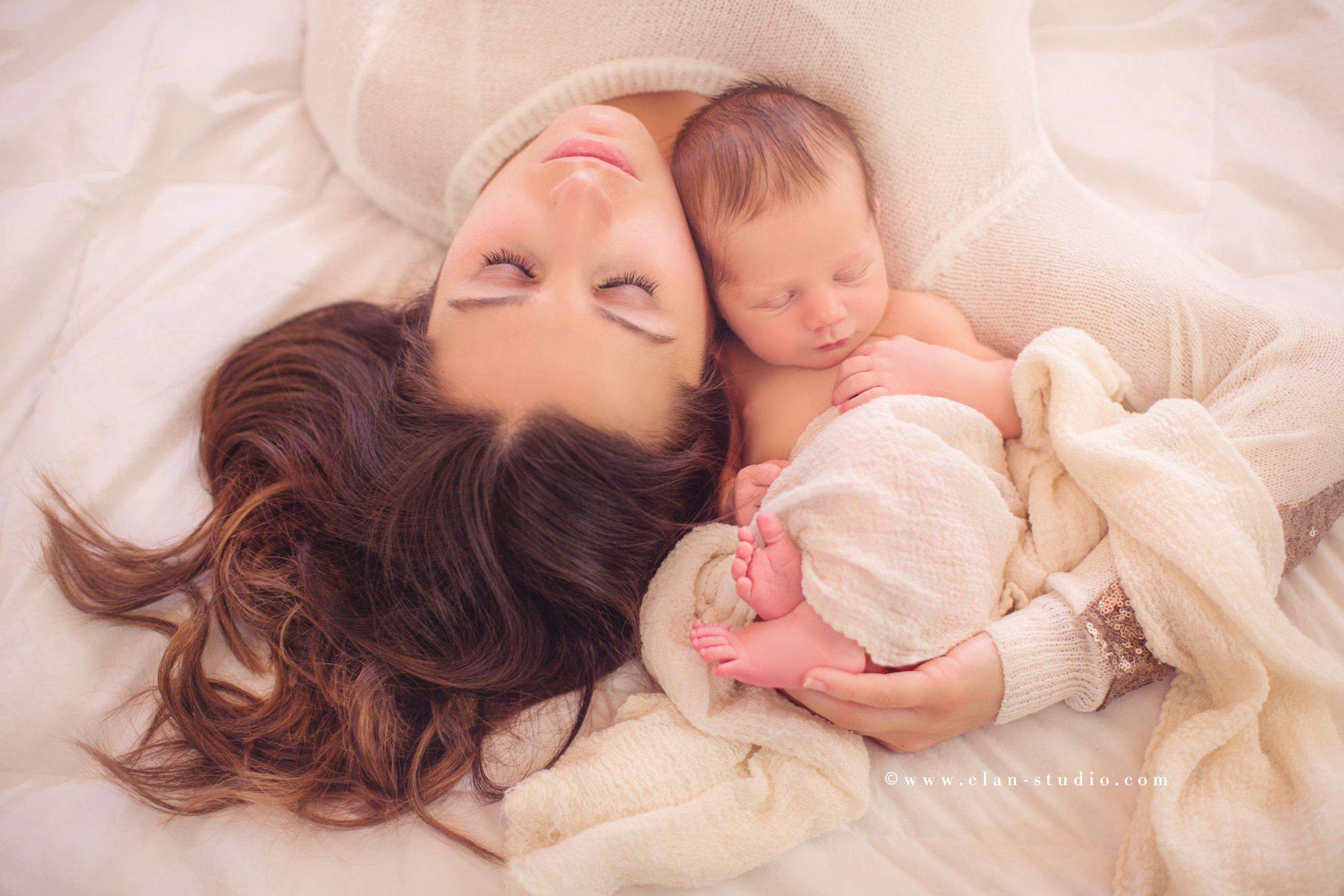 mother cradling newborn baby on a bed, creamy motherhood portrait edit, Elan Studio