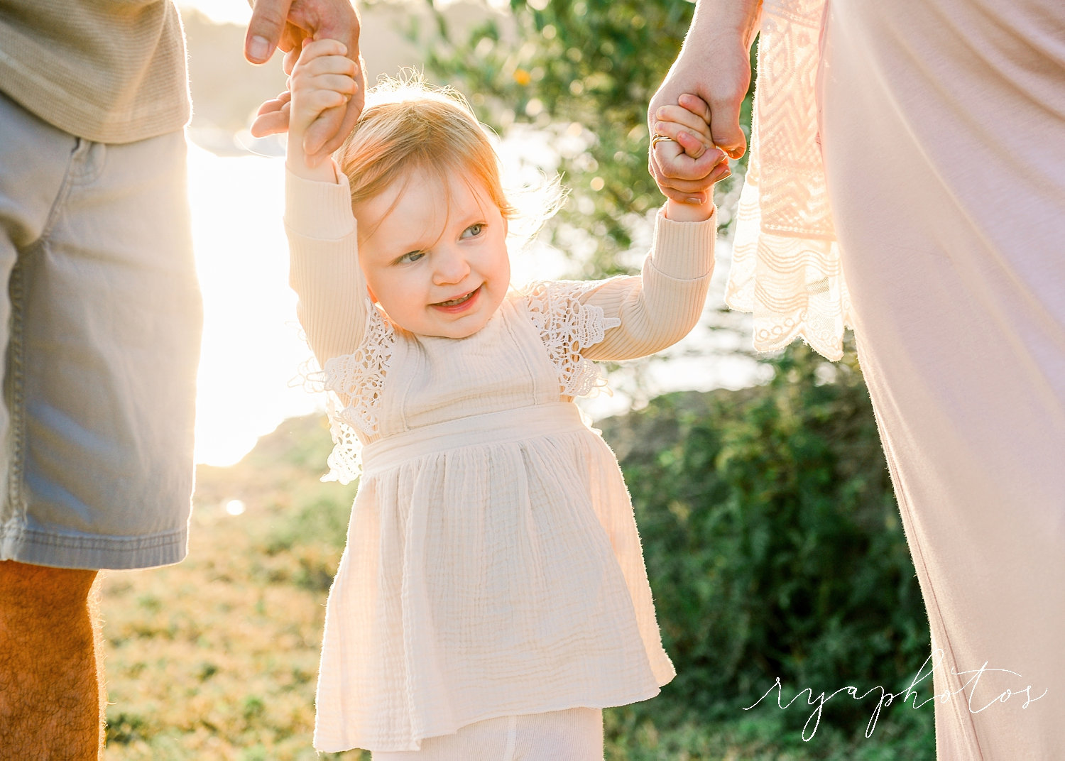 smiling toddler holding mom and dad's hands, bohemian family maternity session, Ryaphotos