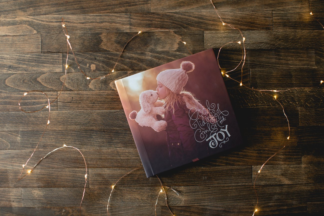good tidings of comfort and joy lettering, twinkle lights, wood table, Miller's Signature Book