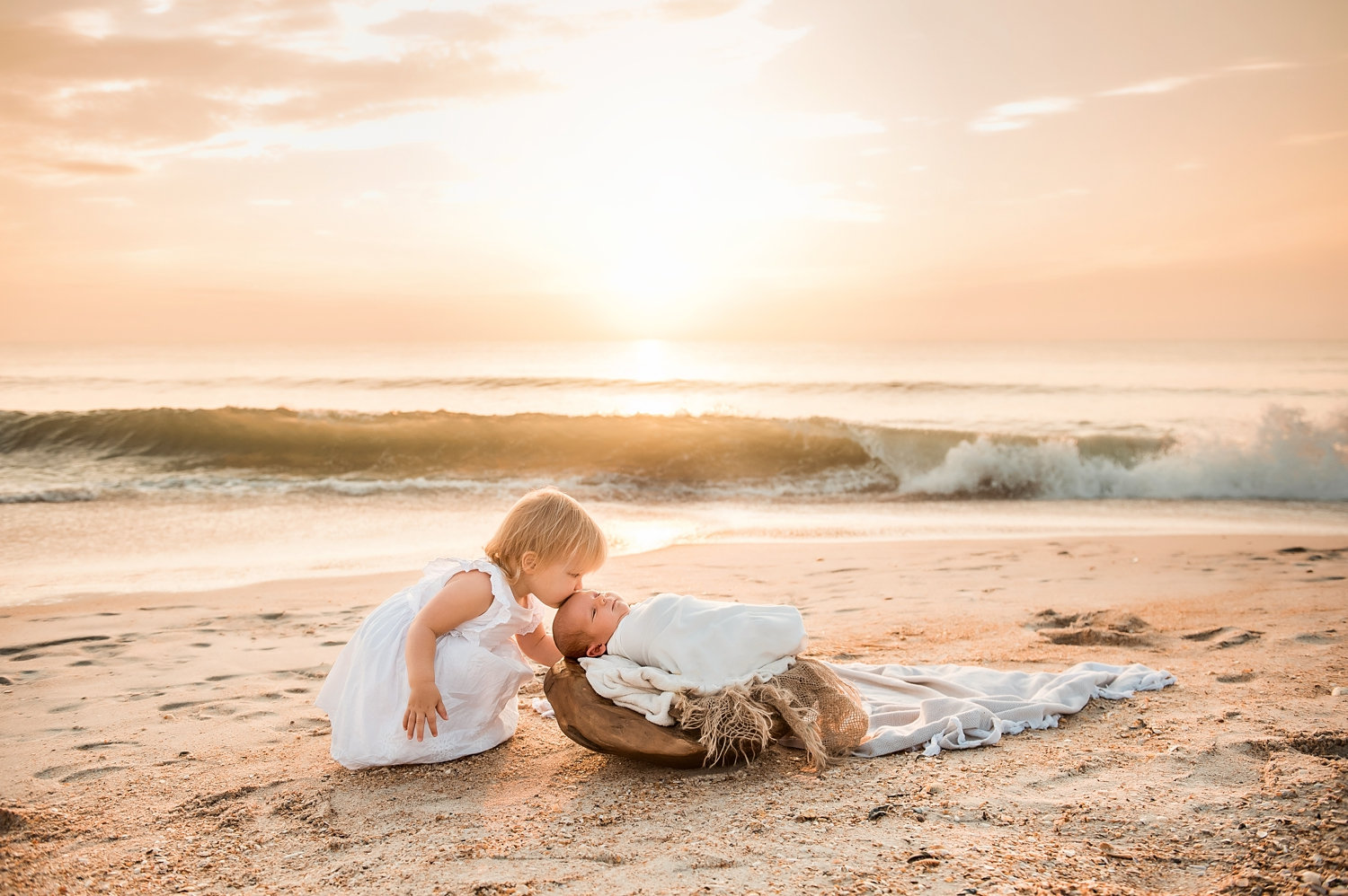 little girl kissing newborn baby sister on her forehead, the waves are rolling in the background, the sun is coming up over the Atlantic ocean