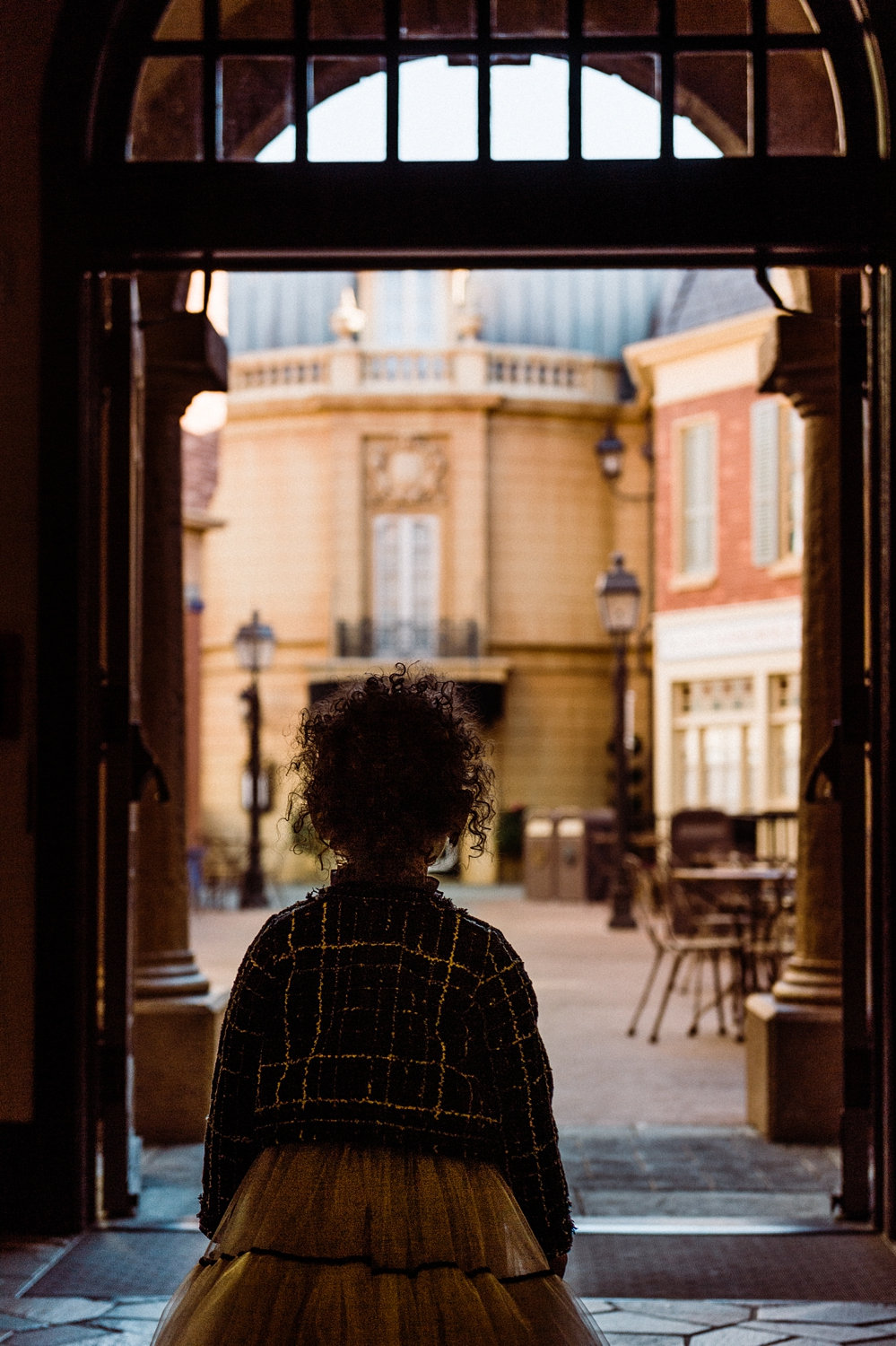 curly haired little girl standing in a tunnel, EPCOT, French pavilion